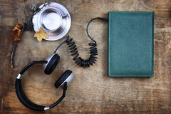 Audiobook headphones and book on wooden table Stock Photos