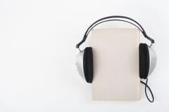 Audiobook på vit bakgrund Den satta hörlurar bokar, den tomma räkningen, kopieringsutrymme för annonstext Avståndsutbildning som  Arkivbilder