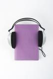 Audiobook på vit bakgrund Den satta hörlurar bokar, den tomma räkningen, kopieringsutrymme för annonstext Avståndsutbildning som  Arkivfoton