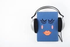 Audiobook på vit bakgrund Hörlurar som sätts över den blåa inbundna boken, bokar, den tomma räkningen, kopieringsutrymme för anno Royaltyfria Foton