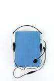 Audiobook på vit bakgrund Hörlurar som sätts över den blåa inbundna boken, bokar, den tomma räkningen, kopieringsutrymme för anno Arkivfoton