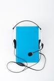 Audiobook på vit bakgrund Hörlurar som sätts över den blåa inbundna boken, bokar, den tomma räkningen, kopieringsutrymme för anno Fotografering för Bildbyråer