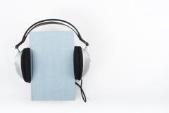 Audiobook på vit bakgrund Hörlurar som sätts över den blåa inbundna boken, bokar, den tomma räkningen, kopieringsutrymme för anno Royaltyfri Bild