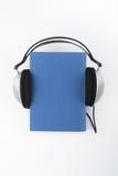 Audiobook på vit bakgrund Hörlurar som sätts över den blåa inbundna boken, bokar, den tomma räkningen, kopieringsutrymme för anno Arkivfoto