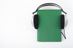 Audiobook på vit bakgrund Hörlurar som sätts över den gröna inbundna boken, bokar, den tomma räkningen, kopieringsutrymme för ann Royaltyfri Bild