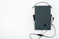 Audiobook på vit bakgrund Hörlurar som sätts över den gröna inbundna boken, bokar, den tomma räkningen, kopieringsutrymme för ann Fotografering för Bildbyråer