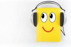Audiobook på vit bakgrund Hörlurar som sätts över den gula inbundna boken, bokar, den tomma räkningen, kopieringsutrymme för anno Royaltyfri Foto