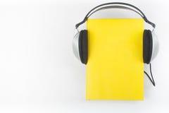 Audiobook på vit bakgrund Hörlurar som sätts över den gula inbundna boken, bokar, den tomma räkningen, kopieringsutrymme för anno Arkivfoton