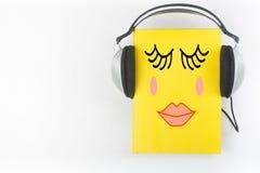 Audiobook på vit bakgrund Hörlurar som sätts över den gula inbundna boken, bokar, den tomma räkningen, kopieringsutrymme för anno Arkivbild