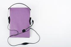 Audiobook på vit bakgrund Hörlurar som sätts över den purpurfärgade inbundna boken, bokar, den tomma räkningen, kopieringsutrymme Arkivfoton
