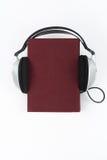 Audiobook på vit bakgrund Hörlurar som sätts över den röda inbundna boken, bokar, den tomma räkningen, kopieringsutrymme för anno Royaltyfria Foton