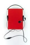 Audiobook på vit bakgrund Hörlurar som sätts över den röda inbundna boken, bokar, den tomma räkningen, kopieringsutrymme för anno Royaltyfri Bild