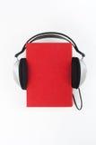 Audiobook på vit bakgrund Hörlurar som sätts över den röda inbundna boken, bokar, den tomma räkningen, kopieringsutrymme för anno Fotografering för Bildbyråer