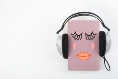 Audiobook på vit bakgrund Hörlurar som sätts över den rosa inbundna boken, bokar, den tomma räkningen, kopieringsutrymme för anno Royaltyfri Fotografi