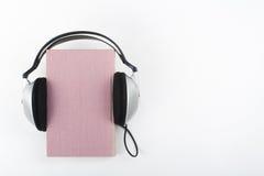 Audiobook på vit bakgrund Hörlurar som sätts över den rosa inbundna boken, bokar, den tomma räkningen, kopieringsutrymme för anno Royaltyfria Foton