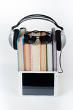 Audiobook sur le fond blanc Les écouteurs ont mis au-dessus de la pile de livres colorés, la couverture vide, l'espace de copie p Image libre de droits