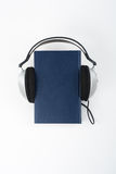 Audiobook on white background. Headphones put over blue hardback book, empty cover, copy space for ad text. Distance royalty free stock image