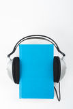 Audiobook on white background. Headphones put over blue hardback book, empty cover, copy space for ad text. Distance royalty free stock photos