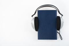 Audiobook on white background. Headphones put over blue hardback book, empty cover, copy space for ad text. Distance Stock Photos