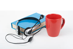 Audiobook on white background. Headphones put over blue hardback book, empty cover, red cup, copy space for ad text Royalty Free Stock Image