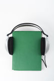 Audiobook on white background. Headphones put over green hardback book, empty cover, copy space for ad text. Distance Royalty Free Stock Photos