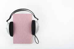 Audiobook on white background. Headphones put over pink hardback book, empty cover, copy space for ad text. Distance Royalty Free Stock Photos
