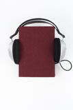 Audiobook on white background. Headphones put over red hardback book, empty cover, copy space for ad text. Distance Royalty Free Stock Photos