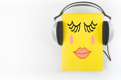 Audiobook on white background. Headphones put over yellow hardback book, empty cover, copy space for ad text. Distance stock photography