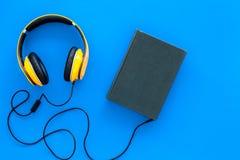 Audiobooks begrepp Hörlurar förbindelse med inbunden bokboken med den tomma räkningen på blått utrymme för kopia för bästa sikt f Arkivfoton