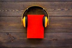 Audiobooks begrepp Hörlurar som sätts över inbunden bokboken med den tomma räkningen på mörkt träutrymme för kopia för bästa sikt Fotografering för Bildbyråer