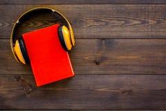 Audiobooks begrepp Hörlurar som sätts över inbunden bokboken med den tomma räkningen på mörkt träutrymme för kopia för bästa sikt Royaltyfria Bilder