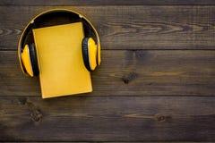 Audiobooks begrepp Hörlurar som sätts över inbunden bokboken med den tomma räkningen på mörkt träutrymme för kopia för bästa sikt Royaltyfri Foto