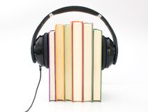Audiobooks concept. Headphones put over book and white background stock image