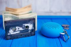 Audiocassette with stack of dollars and portable bluetooth speak. Er with coins close-up. Piracy, copyright violation, price reduction, progress, affordable Stock Image