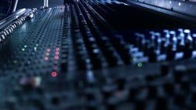 Audioingenieur het aanpassen knoppen en faders op zijn het mengen zich consolebureau tijdens een levende gebeurtenis stock videobeelden