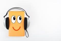 Audiolibro su fondo bianco Le cuffie si impore libro giallo della libro con copertina rigida, svuotano la copertura, copiano lo s Fotografia Stock