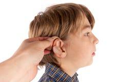 Audiologis die een gehoorapparaat opnemen in een jong jongens geduldig ` s oor stock afbeeldingen