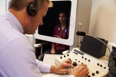 Audiologist de Test van Carrying Out Hearing aangaande Vrouwelijke Patiënt royalty-vrije stock afbeelding