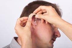 Audiologist die een mensenpatiënt passen met gehoorapparaat royalty-vrije stock foto