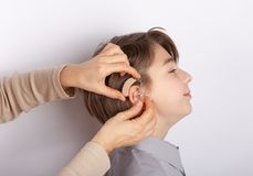 Audiologist fitting hearing aid on a smilling young boy`s ear.  stock photography