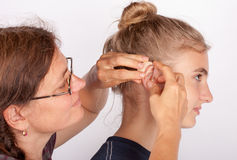 Audiologist and her patient with hearing aid. Audiologist fitting a young women patient with a behind-the-ear hearing aid royalty free stock photo