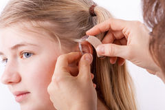 Audiologist inserting a hearing aid Royalty Free Stock Image