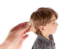 Audiologist ` s hand die een gehoorapparaat voor een jonge jongen houden stock fotografie