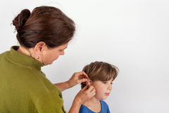 Audiologist woman fitting a young boy with a hearing aid Royalty Free Stock Image