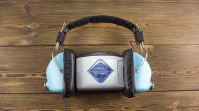 Audiospeler en hoofdtelefoons op een houten vignet als achtergrond stock foto
