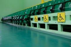 Auditório com fileiras do assento verde As áreas deficientes são identificadas por meio de sinais amarelos especiais imagem de stock royalty free