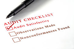 Audit checklist, with tick against on white paper. Stock Image