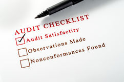 Audit checklist, with tick against on white paper. Stock Photo