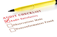 Audit checklist, with tick against on white paper. Stock Images