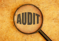 Audit. Magnifying glass focused on the word audit royalty free stock photo